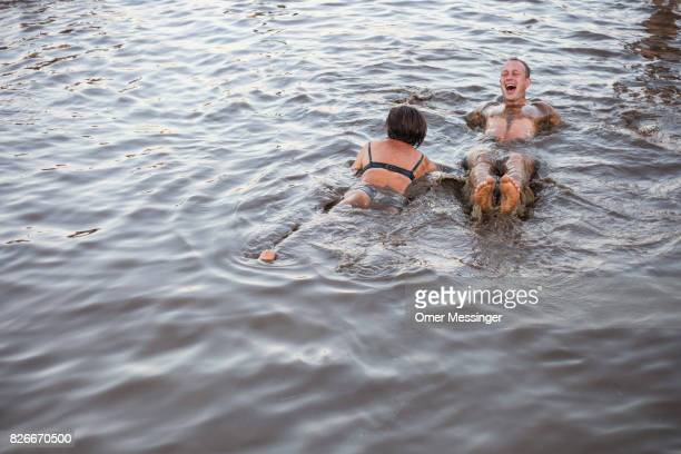 A man and a woman lay in a pool of muddy water at the 2017 Woodstock Festival Poland on August 4 2017 in Kostrzyn Poland The threeday rock music...