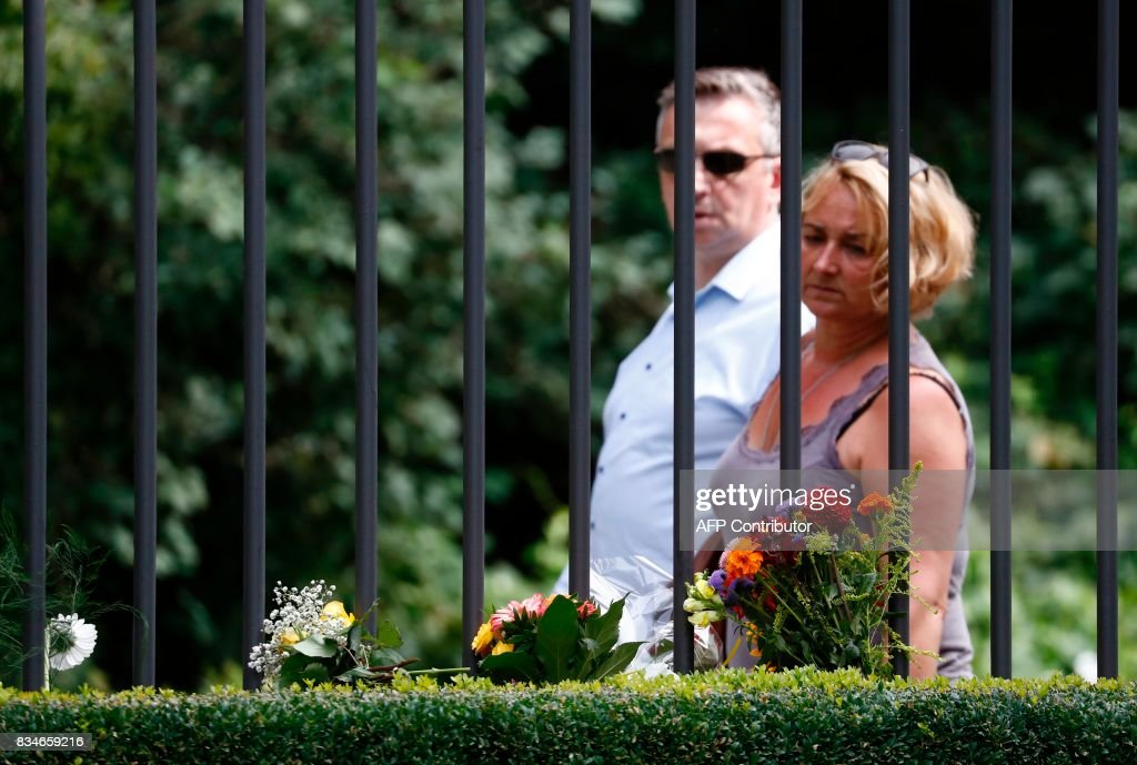 A man and a woman look at flowers at the fence of the Spanish embassy in Berlin, on August 18, 2017 in tribute to victims of the Barcelona attack. A driver rammed a van into a crowd on Barcelona's famous avenue Las Ramblas on August 17, 2017 afternoon, while eight hours later, an Audi A3 car ploughed into pedestrians in the seaside city of Cambrils. / AFP PHOTO / Odd ANDERSEN