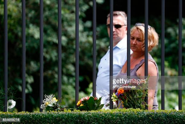A man and a woman look at flowers at the fence of the Spanish embassy in Berlin on August 18 2017 in tribute to victims of the Barcelona attack A...