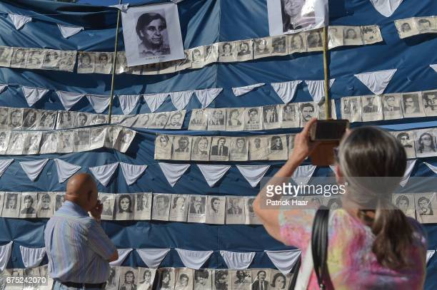 A man and a woman look at the flag with the photographs of the disappeared during last military regime as part of an act to conmemorate the 40th...