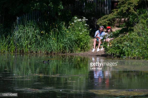 Man and a woman look at the wildlife in a pond on Parliament Hill on May 29, 2020 in London, England. From Monday, groups of up to six people from...