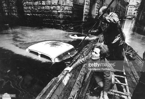 A man and a woman moving by boat along the streets of Florence during the flood Florence November 1966