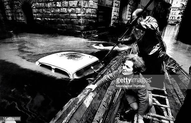 A man and a woman on a boat in the historic center of Florence during the flood of 1966 seeking to avoid a car that floats in water Italy 1966