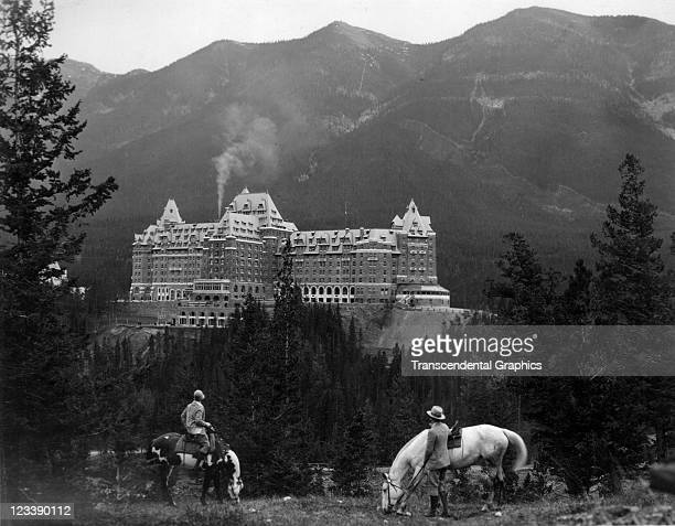 A man and a woman on horseback pause to look at the great Banff Hotel in this photo taken early to mid 20th century in Banff Alberta Canada