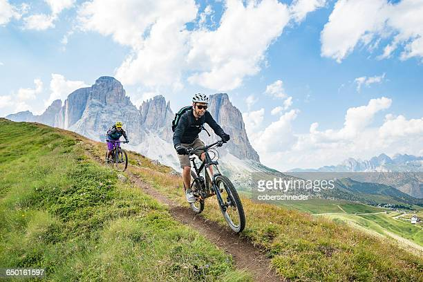 A man and a woman on  mountain bikes racing along trail in the Dolomites,  Val Gardena, Italy