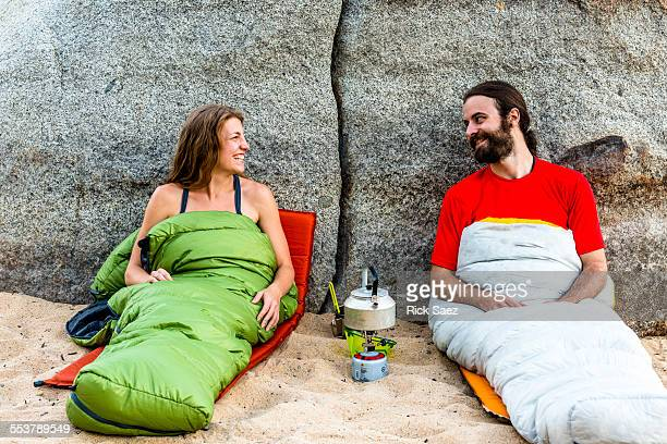 Man and a woman on the beach in sleeping bags laughing