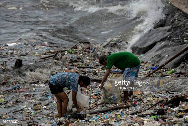 A man and a woman pick up litter on the shores of Manila Bay after a heavy downpour caused by Severe Tropical Storm Maliksi east of the Philippines...