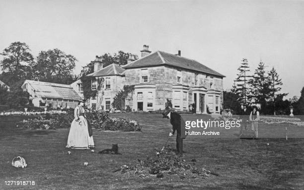Man and a woman playing croquet on the lawn at Adwell House in Adwell, Oxfordshire, circa 1875. A dog lays on on the lawn as the couple play, as two...