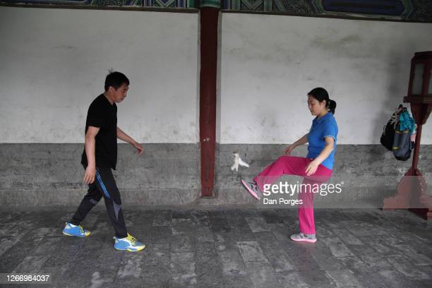 A man and a woman playJianzi in the Temple of Heaven compund it is a traditional Chinese national sport game in which players aim to keep a heavily...