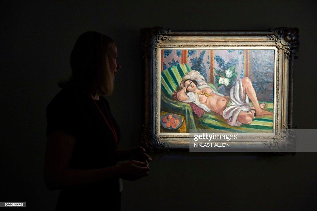 A man and a woman pose with 'Odalisque couchae aux magnolias', 1923, by French artist Henri Matisse during a preview for the Peggy and David Rockefeller art collection sale at Christie's auction house in London on February 21, 2018. The collection of Peggy and David Rockefeller will be offered for sale at Christies Rockefeller Center Galleries in New York from May 7-11, 2018. Proceeds from the sale will benefit selected charities. / AFP PHOTO / NIKLAS HALLE