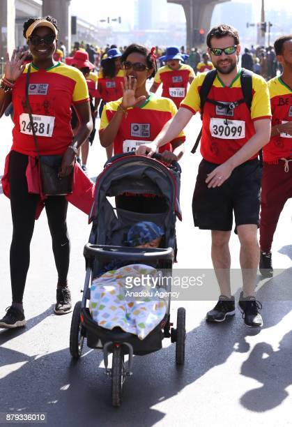 A man and a woman push a baby stroller during the Great Ethiopian Run at Adwa Square in Addis Ababa Ethiopia on November 26 2017 Total of 44000...
