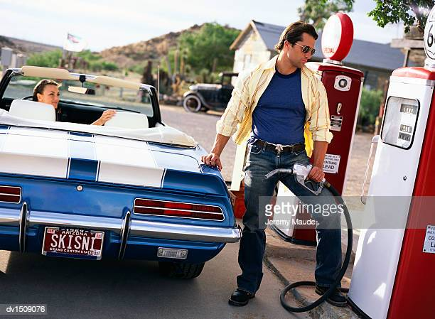 Man and a Woman Refuelling a Classic Convertible in a Petrol Station