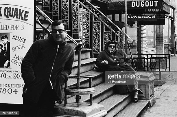 A man and a woman relax outside a building on MacDougal Street Greenwich Village New York City USA circa 1966