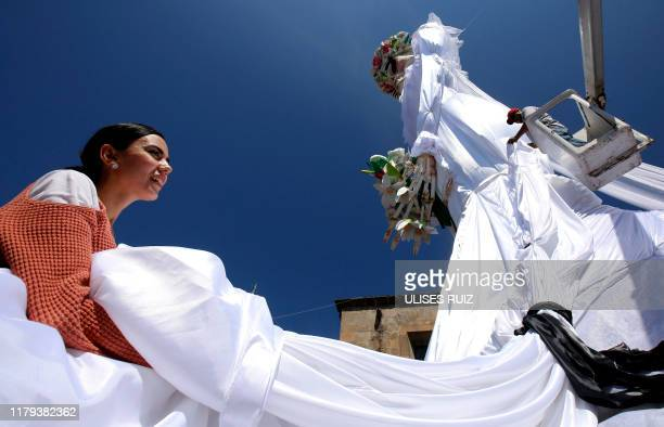 A man and a woman set up a 20meterhigh Catrina figure the biggest in the world dressed up as a bride and the Catrin her groom in the main square of...