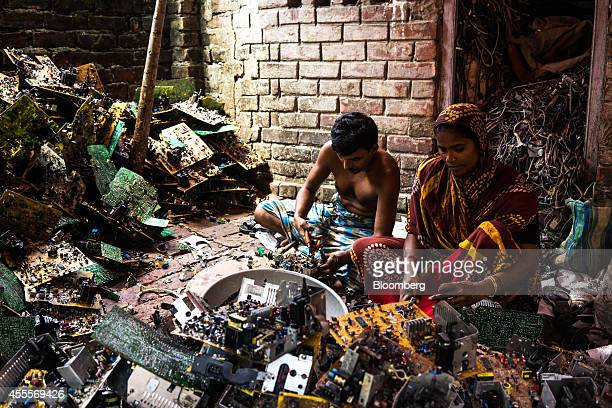 A man and a woman sit among piles of electronic waste as they dismantle computer peripherals at a family compound of houses in Sangrampur village...
