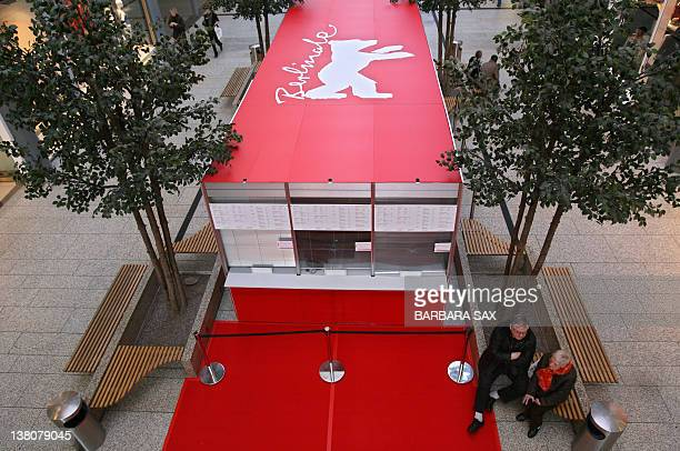 A man and a woman sit in front of a ticket booth with a Berlinale bear the logo of Berlin's film festival on February 4 2008 at a shopping center in...