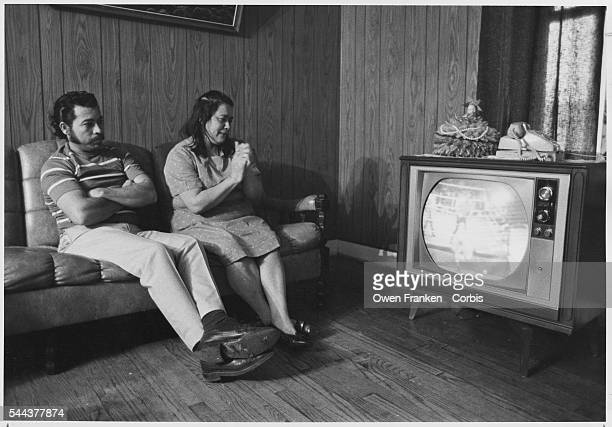 A man and a woman sit in their living room and watch a wrestling match on television