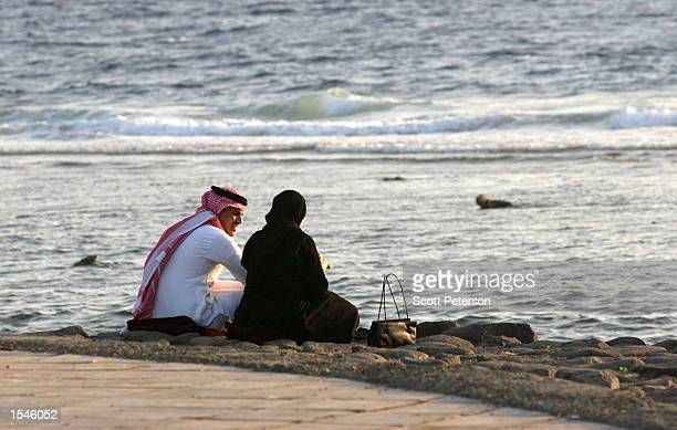 A man and a woman sit on a beach May 20 2002 in Jeddah Saudi Arabia Strictly conservative rules for social contact between young men and women and an...