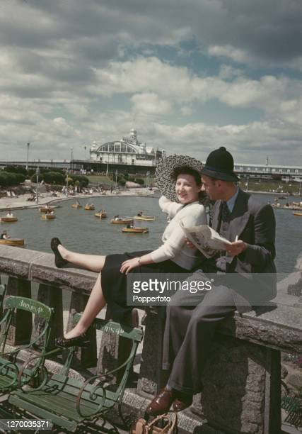 Man and a woman sit on a stone parapet wall beside the boating lake and pier pavilion as they enjoy a summer holiday break at Southend-on-Sea in...
