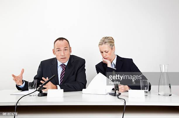 A man and a woman sitting at a desk with microphones and documents