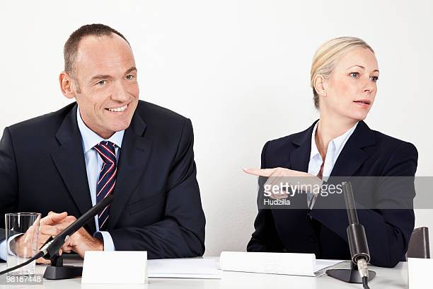 A man and a woman sitting at a desk with microphones