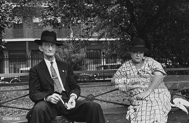A man and a woman sitting on a metal park bench the man is wearing a suit and tie along with a hat the woman is wearing a patterned dress and a hat a...
