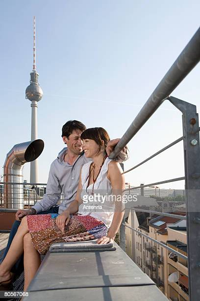 A man and a woman sitting together on a rooftop terrace