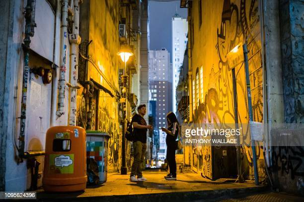 A man and a woman stand in an alleyway in the Central district of Hong Kong on February 8 2019