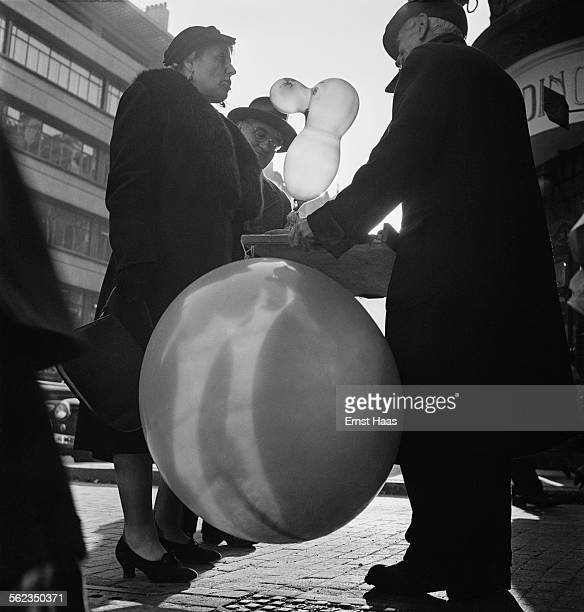 A man and a woman talking to a street vendor near Piccadilly London circa 1953