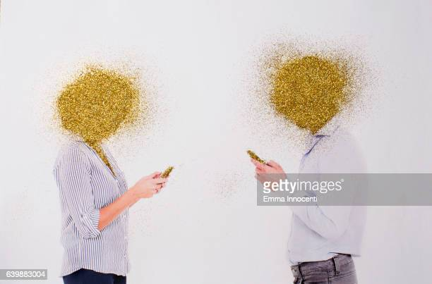 Man and a woman texting with golden heads