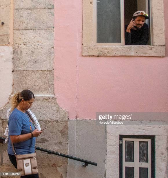 A man and a woman use their cellphones in Calçada da Bica Pequena Santa Catarina historical neighborhood a permanent attraction for tourists on...