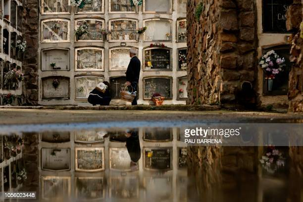 A man and a woman visit the graves of loved ones at the Montjuic Cemetery on All Saints' Day in Barcelona on November 1 2018