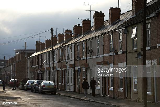 A man and a woman walk along the Eastwood area of Rotherham South Yorkshire North England on October 6 2014 An inquiry revealed on August 26 2014...