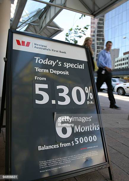 A man and a woman walk by an interest rate sign outside a Westpac Bank branch in Sydney Wednesday March 31 2004 The rate of increase in Australian...