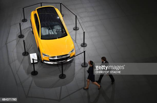 A man and a woman walk past an Audi car on display during the German car maker's annual general meeting in Neckarsulm southern Germany on May 18 2017...