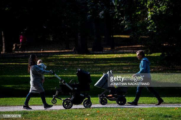 Man and a woman walk their babies in baby strollers at Humlegarden in Stockholm on September 24, 2020. - While France has just increased paternity...