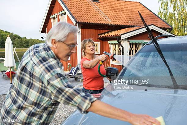 a man and a woman washing their car outside their house - couples showering stock pictures, royalty-free photos & images