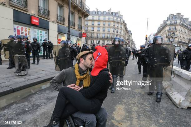 A man and a woman wearing the Phrygian cap of the French Republic are kissing in front of antiriot gendarmes in Paris on January 12 2019 during an...