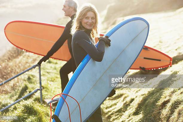 a man and a woman with surfboards - young at heart stock pictures, royalty-free photos & images
