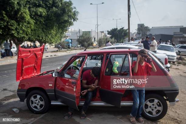 A man and a young boy wait to sell their car at a used car market in Gaza City Gaza For the past ten years Gaza residents have lived with constant...