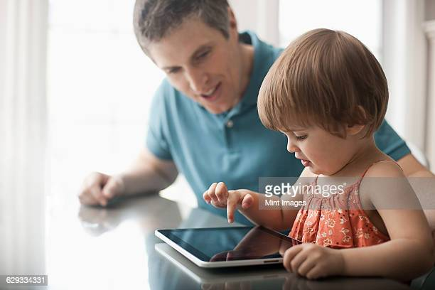 A man and a young child sitting looking at a digital tablet and touching the screen.
