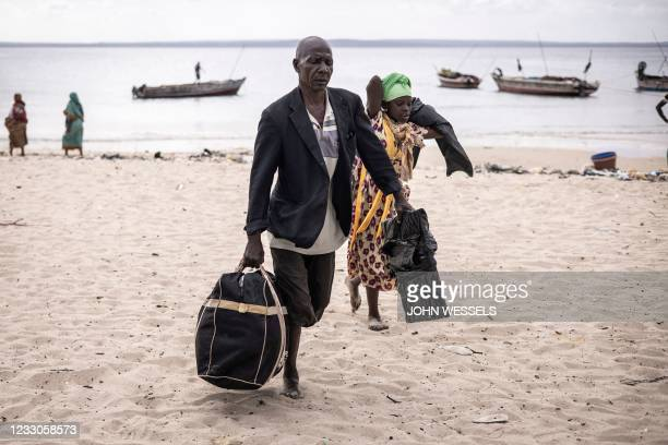 Man and a young girl carry their belongings off a boat as they arrive at Paquitequete beach in Pemba on May 22 after fleeing Palma by boat with forty...