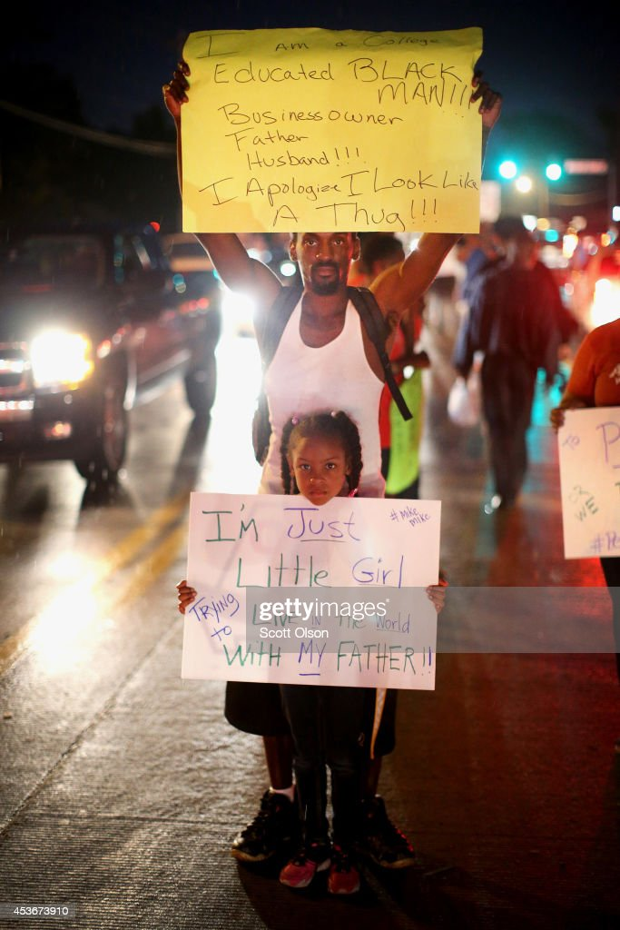 A man and a young girl hold up posters with protest slogans