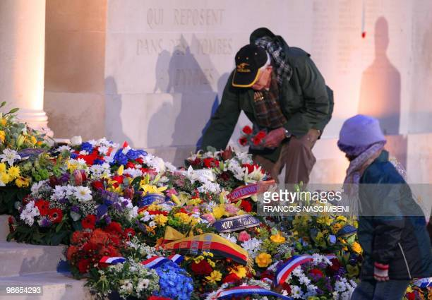 A man and a young girl place flowers at the foot of a memorial wall during a dawn service commemorating Anzac Day on the WWI battlefield of...