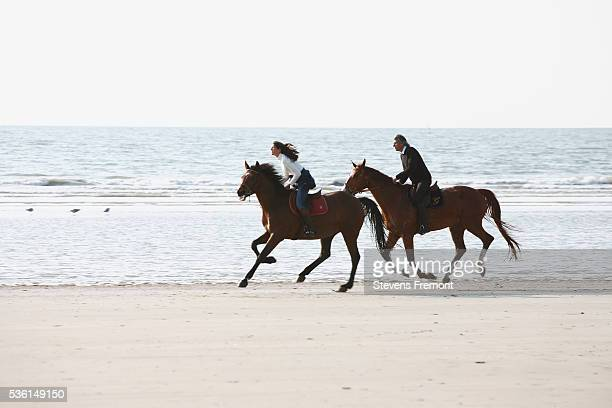 Man and a young woman riding horses on the beach of Deauville