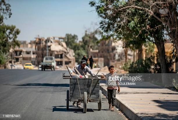 Man and a youngster push a cart in the northern Syrian city of Raqa, the former Syrian capital of the Islamic State group, on August 21, 2019. - The...