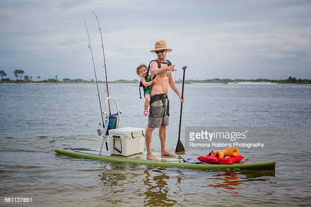 Man and baby daughter standup paddleboarding in the sound, Fort Walton, Florida, USA