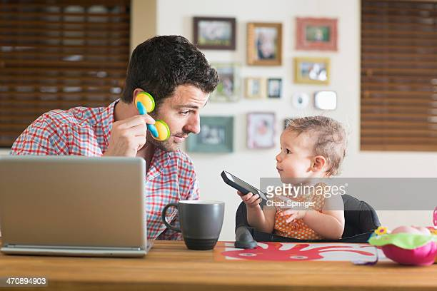 Man and baby sitting at kitchen counter playing with smartphone and toy phone