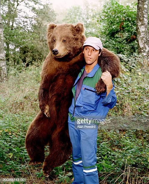 man and bear embracing in woods - beer stockfoto's en -beelden