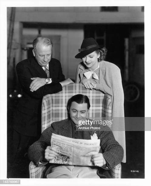 Man and Betty Furness looking over a seated Robert Young in a scene from the film 'The Three Wise Guys', 1936.